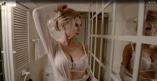 Charlotte seductively flashes the fullness of her assets as she walks along the hallway with mirrors on one side