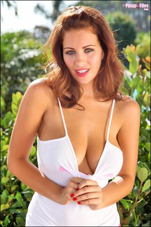 Holly Peers soaks herself with a garden hose in a white shirt